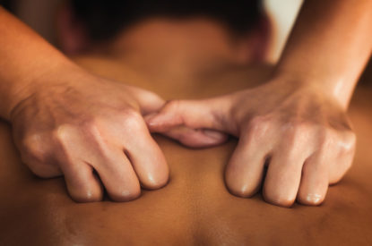 Physiotherapist massaging male patient with injured back muscle. Sports injury treatment.