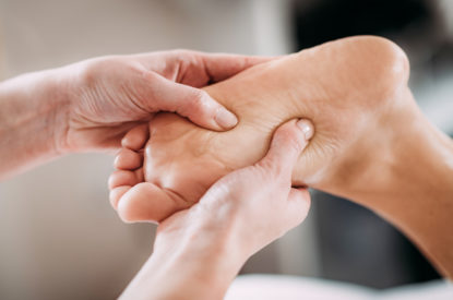 Physiotherapist massaging female patient with injured foot. Sports injury treatment.