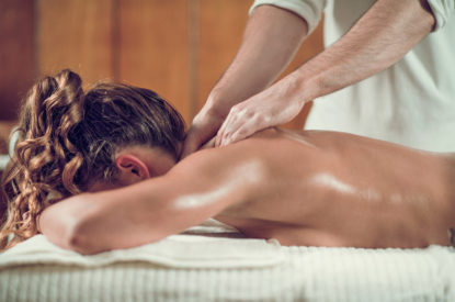 Close up of young woman with oiled skin having relaxing shoulders and neck massage