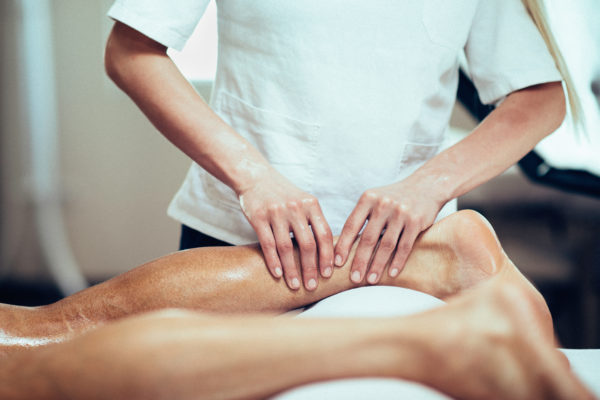 Sports Massage - Massage therapist working with patient, massaging his calves. Toned image.